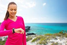 Mujer sonriente con el reloj del ritmo cardíaco en la playa Foto de archivo libre de regalías