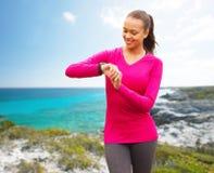 Mujer sonriente con el reloj del ritmo cardíaco en la playa Foto de archivo