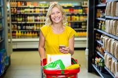 Mujer sonriente con el smartphone que empuja la carretilla en pasillo Fotos de archivo