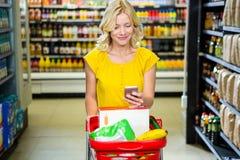 Mujer sonriente con el smartphone que empuja la carretilla en pasillo Foto de archivo libre de regalías