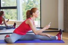 Mujer sonriente con el smartphone que estira en gimnasio Foto de archivo