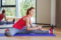 Mujer sonriente con el smartphone que estira en gimnasio Imagen de archivo libre de regalías