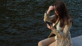 Mujer sonriente con el smartphone que se sienta contra el agua metrajes