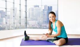 Mujer sonriente con el smartphone que se sienta sobre gimnasio Imágenes de archivo libres de regalías