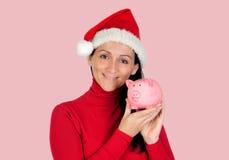 Mujer sonriente con el sombrero de la Navidad y una hucha Imágenes de archivo libres de regalías