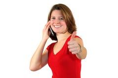 Mujer sonriente con el teléfono celular y los pulgares para arriba Foto de archivo libre de regalías