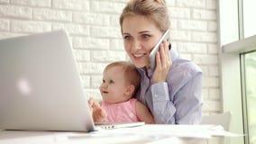 Mujer sonriente con el teléfono de discurso del niño Madre feliz del negocio que trabaja en casa almacen de video