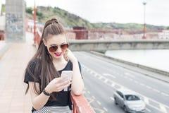 Mujer sonriente con el teléfono en la calle Foto de archivo libre de regalías