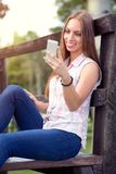 Mujer sonriente con el teléfono móvil imagen de archivo libre de regalías
