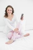Mujer sonriente con el teléfono móvil en cama Fotos de archivo libres de regalías