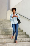 Mujer sonriente con el teléfono móvil que camina abajo de los pasos Fotos de archivo libres de regalías