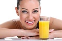 Mujer sonriente con el zumo de naranja Imagen de archivo libre de regalías