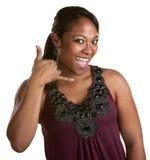 Mujer sonriente con gesto del teléfono Imagen de archivo