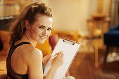 Mujer sonriente con horario del tablero y de la comida del edificio de la pluma imágenes de archivo libres de regalías
