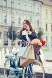 Mujer sonriente con la bicicleta que habla en el teléfono móvil fotografía de archivo