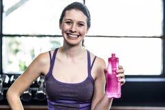 Mujer sonriente con la botella de presentación del agua Fotos de archivo