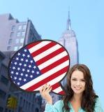 Mujer sonriente con la burbuja del texto de la bandera americana Foto de archivo