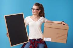 Mujer sonriente con la caja de cartón que mira al tablero en blanco en azul Fotografía de archivo