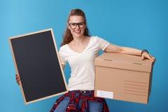 Mujer sonriente con la caja de cartón que muestra al tablero en blanco en azul Fotografía de archivo libre de regalías