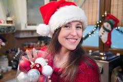 Mujer sonriente con la caja de ornamentos de la Navidad Fotografía de archivo