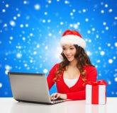 Mujer sonriente con la caja de regalo y el ordenador portátil Imagen de archivo