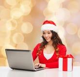 Mujer sonriente con la caja de regalo y el ordenador portátil Fotografía de archivo