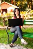 Mujer sonriente con la computadora portátil Imágenes de archivo libres de regalías