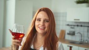 Mujer sonriente con la copa en cocina nacional Muchacha principal roja almacen de metraje de vídeo