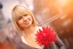 Mujer sonriente con la flor Foto de archivo libre de regalías