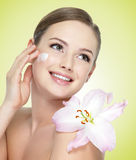 Mujer sonriente con la flor que aplica la crema cosmética en cara Fotografía de archivo libre de regalías