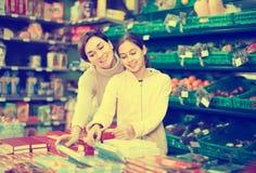 Mujer sonriente con la hija que elige las galletas en supermercado Imagen de archivo