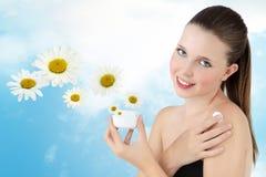 Mujer sonriente con la loción poner crema en el cielo del fondo Foto de archivo libre de regalías