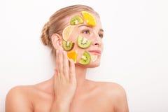 Mujer sonriente con la máscara de la fruta en su cara aislada Foto de archivo libre de regalías