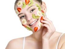 Mujer sonriente con la máscara facial de la fruta en cara Foto de archivo