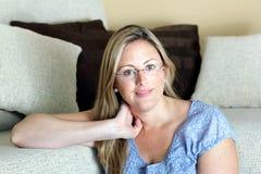 Mujer sonriente con la mano en la cabeza que se sienta en sala de estar Fotografía de archivo libre de regalías