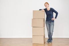 Mujer sonriente con la mudanza o cajas de almacenamiento Imágenes de archivo libres de regalías