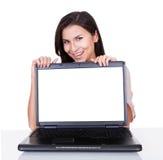 Mujer sonriente con la pantalla en blanco del ordenador portátil Foto de archivo
