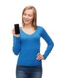 Mujer sonriente con la pantalla en blanco negra del smartphone Imágenes de archivo libres de regalías