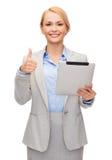 Mujer sonriente con la PC de la tableta que muestra los pulgares para arriba Foto de archivo