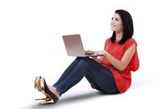 Mujer sonriente con la sentada del ordenador portátil Fotografía de archivo