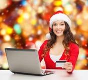 Mujer sonriente con la tarjeta de crédito y el ordenador portátil Fotografía de archivo