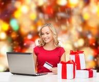Mujer sonriente con la tarjeta de crédito y el ordenador portátil Foto de archivo libre de regalías