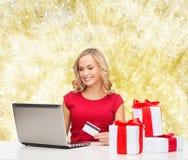 Mujer sonriente con la tarjeta de crédito y el ordenador portátil Foto de archivo