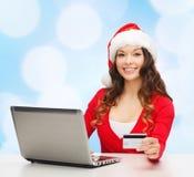 Mujer sonriente con la tarjeta de crédito y el ordenador portátil Imágenes de archivo libres de regalías
