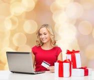 Mujer sonriente con la tarjeta de crédito y el ordenador portátil Imagen de archivo