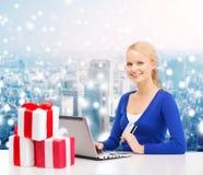 Mujer sonriente con la tarjeta de crédito y el ordenador portátil Fotos de archivo