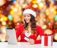 Mujer sonriente con la tarjeta de crédito y la PC de la tableta Fotos de archivo