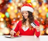 Mujer sonriente con la tarjeta de crédito y la PC de la tableta Fotografía de archivo libre de regalías