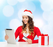 Mujer sonriente con la tarjeta de crédito y la PC de la tableta Foto de archivo
