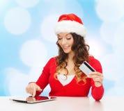 Mujer sonriente con la tarjeta de crédito y la PC de la tableta Fotografía de archivo